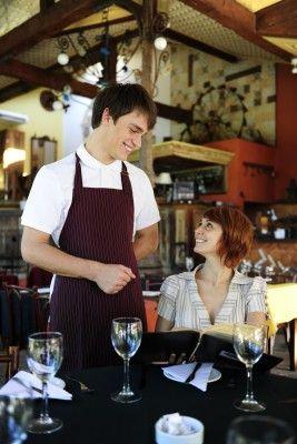 Male waiter waits on female patron.